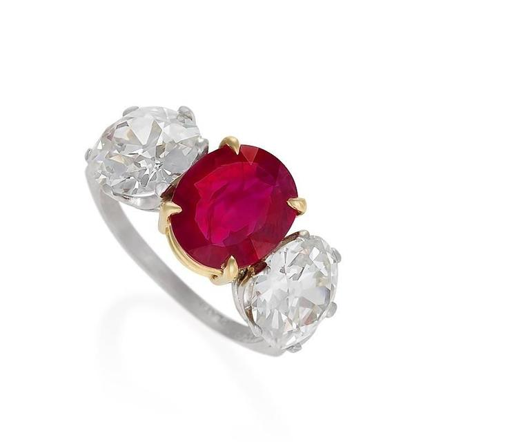 An 18 karat gold and platinum ring with ruby and diamonds. The ring centers on an oval mixed cut Burmese ruby with an approximate weight of 2.56 carats, and two Old European-cut diamonds with an approximate total weight of 5.00 carats,  H/I color,