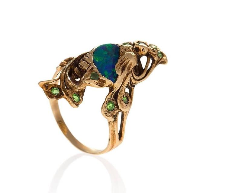 An Art Nouveau 14 karat gold ring with black opal and demantoid garnets by Walton & Co. The ring has a black opal, and 11 round-cut demantoid garmets with an approximate total weight of .22 carats.  The ring is in the form of a peacock with the