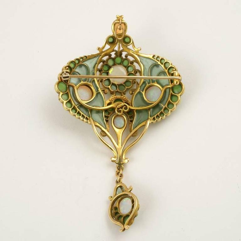 An American Art Nouveau 18 karat gold and enamel pendant brooch with opals and chrysoprase by Marcus & Co.. The pendant brooch has 6 cabochon white opals, 63 cabochon chrysoprase stones and plique-à-jour enamel. Suspended from the brooch is an opal