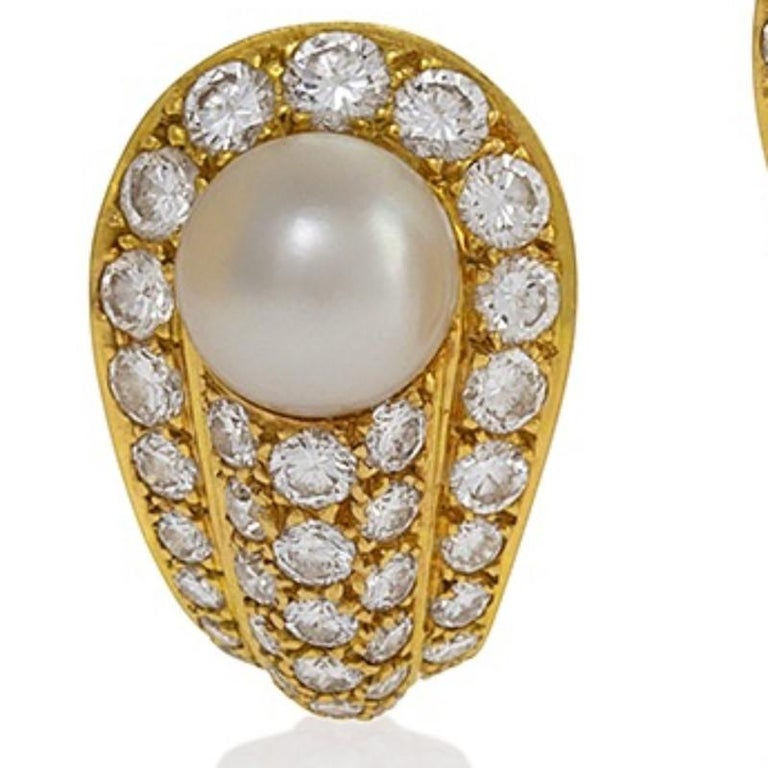 A pair of French Late-20th Century 18 karat gold earrings with pearls and diamonds by Cartier. The earrings center on 8 mm Japanese cultured pearls, surrounded by 74 round brilliant cut diamonds with an approximate total weight of 2.5 carats.  Circa