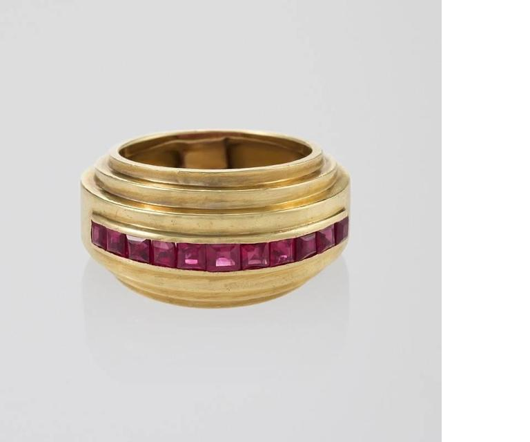 A French Art Deco 18 karat gold ring with rubies by Van Cleef & Arpels. The ring has 11 square-cut rubies with an approximate total weight of 1.32 carats. The ring is designed in a triple stepped, polished gold motif. Circa 1930's.   Similar