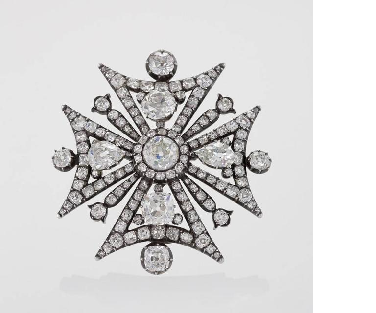 An English Antique 15 karat gold and oxidized silver Maltese cross brooch with diamonds. The brooch has 130 old European-cut and old mine-cut diamonds with an approximate total weight of 18.00 carats including a 2.25 carat center diamond. Fold down