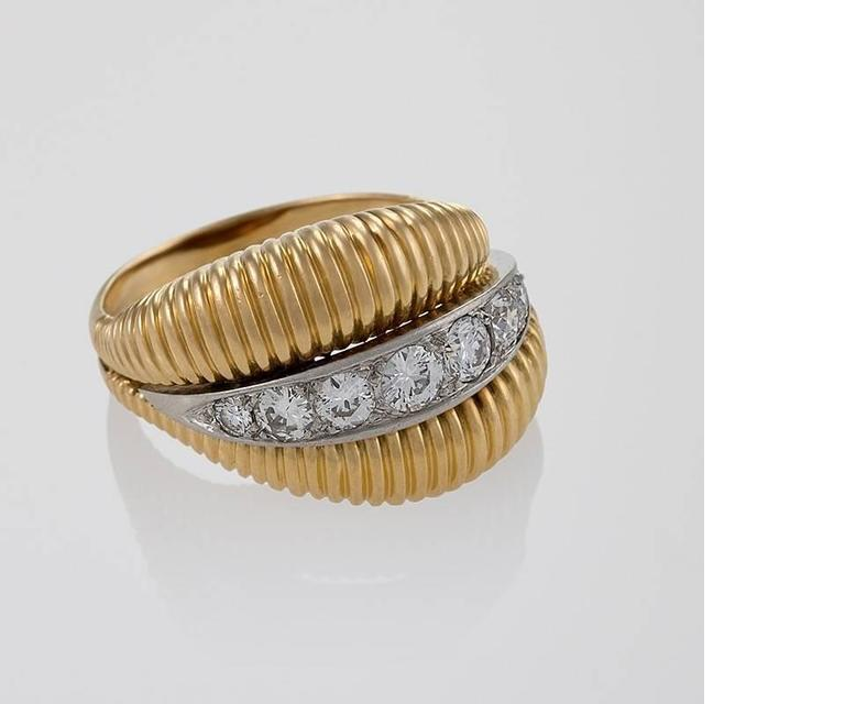 A French Mid-20th Century 18 karat gold and platinum ring with diamonds by Van Cleef & Arpels. The ring has 7 round-cut diamonds with an approximate total weight of .70 carats, G/H color, VS clarity grade. The central diamond set platinum line