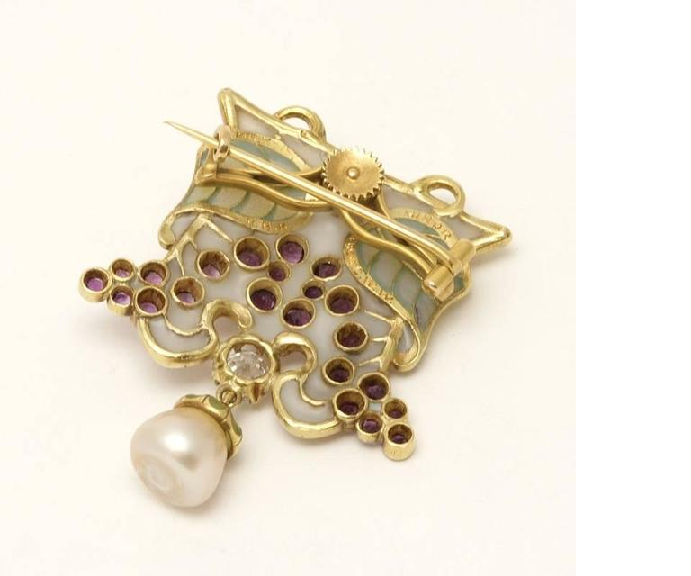 An Art Nouveau 18 karat gold and plique à jour brooch with diamond, amethysts and pearl by Louis Zorra. The brooch has an old mine-cut diamond with an approximate total weight of .65 carat, 21 round bezel-set amethysts with an approximate total