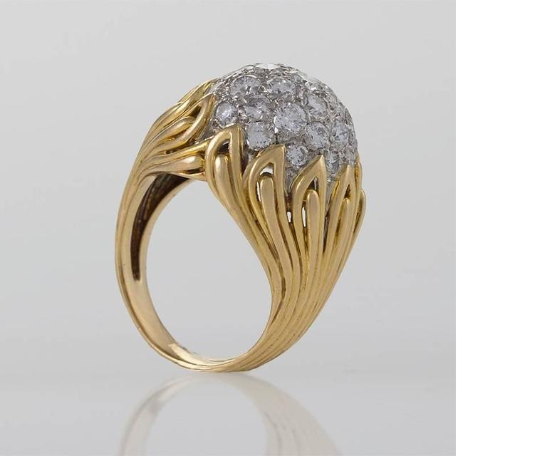 A French Mid-20th Century 18 karat gold ring with diamonds by Van Cleef & Arpels. The ring has 31 round diamonds with an approximate total weight of 2.48 carats. The ring is composed in a modernist flame motif which centers on the diamond set