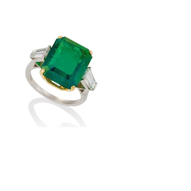 This large and precious nearly nine-carat Colombian emerald estate ring exhibits a classic, slightly bluish-green hue, thanks to the presence of rare trace elements. A timeless design that centers the emerald-cut stone flanked with tapering diamond