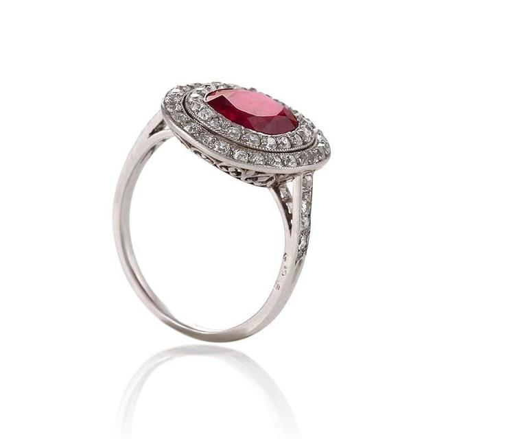 An Early Art Deco platinum ring with ruby and diamonds. The ring has a cushion-cut ruby with an approximate weight of 2.32 carats, and 47 old mine cut diamonds with an approximate total weight of .70 carat.  The center stone carries Gubelin