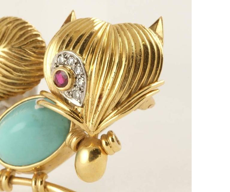 A French Mid-20th Century 18 karat gold and platinum brooch with turquoise, ruby and diamonds by Van Cleef & Arpels. The brooch has a cabochon turquoise body, a round ruby with an approximate total weight of .30 carats, and 5 round diamonds with an