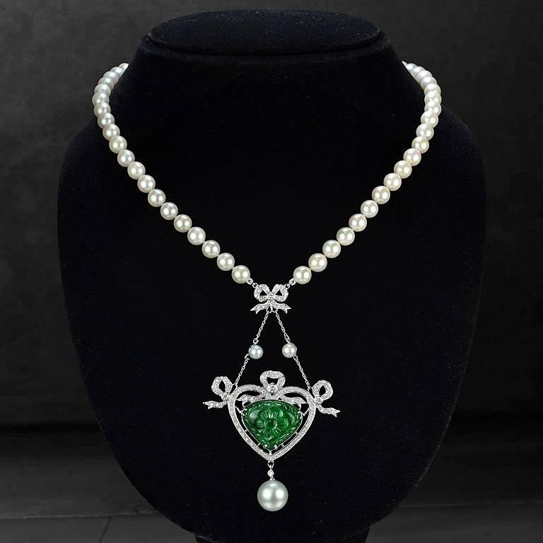 Carved Emerald Trillion Shape from Zambia 13.70 Carat set on 18K White Gold Pendant with Round Cut Diamond 88 pieces 1.11 Carat. Pearl 1 piece 10.60 Carat and 2 pieces 1.50 Carat on top of the Pendant. The pearl strand is Akoya Pearl from Japan