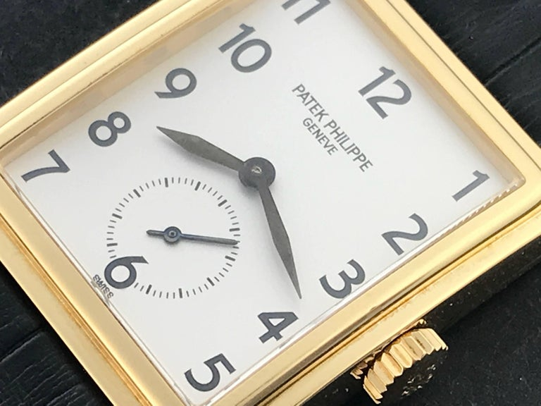 Patek Philippe 18k Yellow Gold Gondolo Mens manual wind Wrist Watch. 18k Yellow Gold case measuring 25 x 32mm diameter. Silvered Dial with black Arabic numerals. Black alligator strap with 18k yellow gold Patek Philippe buckle. Patek Philippe box