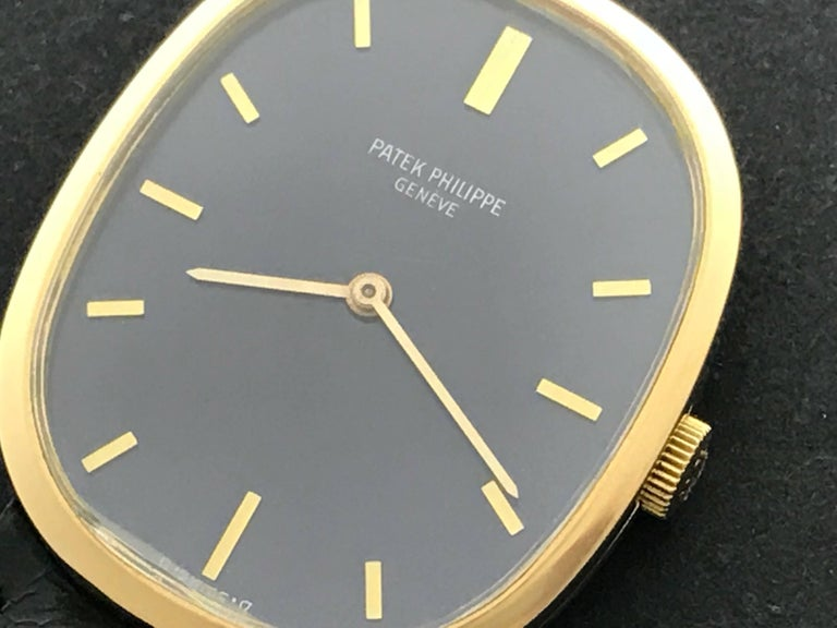 Patek Philippe Men's 3548 Wrist Watch in 18K Yellow Gold.  This timepiece features an 18K yellow Gold ellipse case, measuring 27x32mm in diameter.  Blue Dial with Yellow Gold hour markers. Black strap with 18k Yellow Gold Patek Philippe buckle is