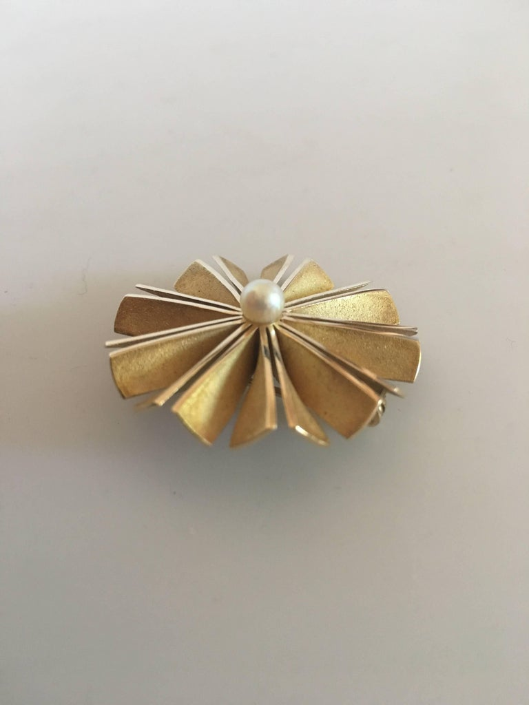 "Hans Hansen 14K Round Gold Brooch with Pearl. Measures 3.3 cm diameter (1 19/64""). Weighs 13 grams (0.45 oz)."