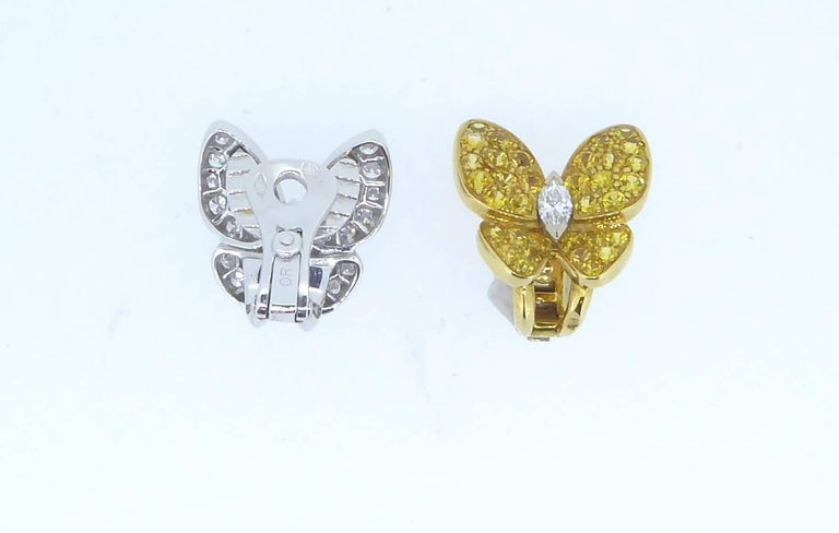 A pair of Van Cleef & Arpels Yellow Sapphire Diamond and Gold Butterfly Earrings. One ear clip with white diamonds set in 18ct white gold and a marquise diamond body. The other ear clip with yellow sapphires set in 18ct yellow gold and a marquise