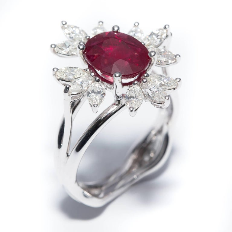 A custom revival of the traditional Halo design, this particular ring has a center stone surrounded by Marquise cut white diamonds totaling 1.10 Carat with a 2.13 Carat Oval Shaped Ruby nice deep color however this particular stone is treated (9 x 7