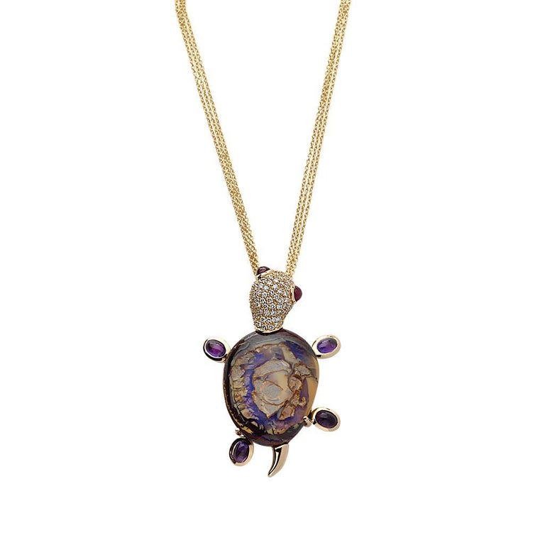 This cute little turtle is crafted in 19.2K yellow gold and set with a boulder opal, white diamonds, rubies and amethysts it is a unique piece because of the shape and colors of the central stone. It was conceived with a triple gold chain. This