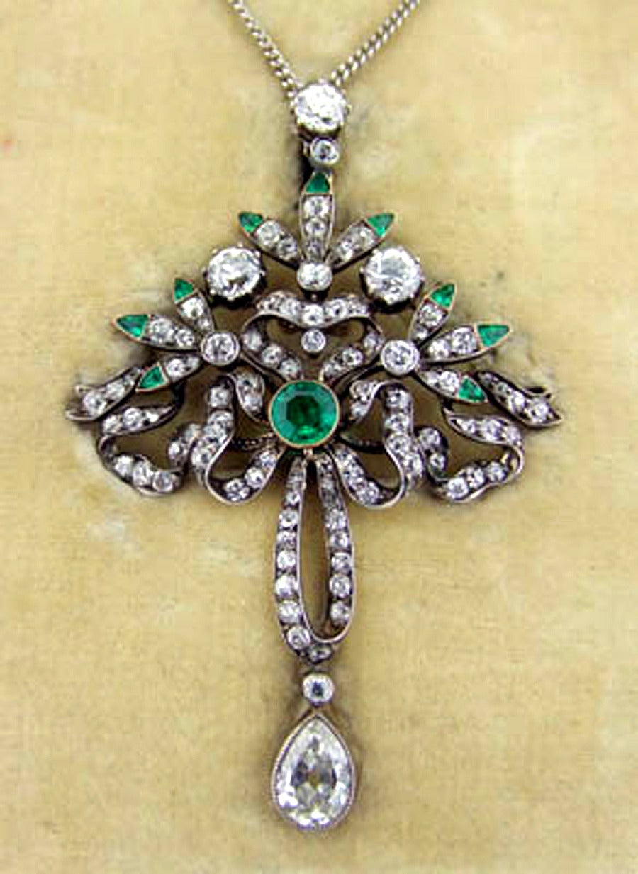 18ct gold and silver set Victorian, Diamond and Emerald Pendant or Brooch circa 1860   Floral and scroll motif design in 18ct yellow gold with emerald tips to the flowers with an articulated pear shaped diamond drop of approx 1.0ct. Very well