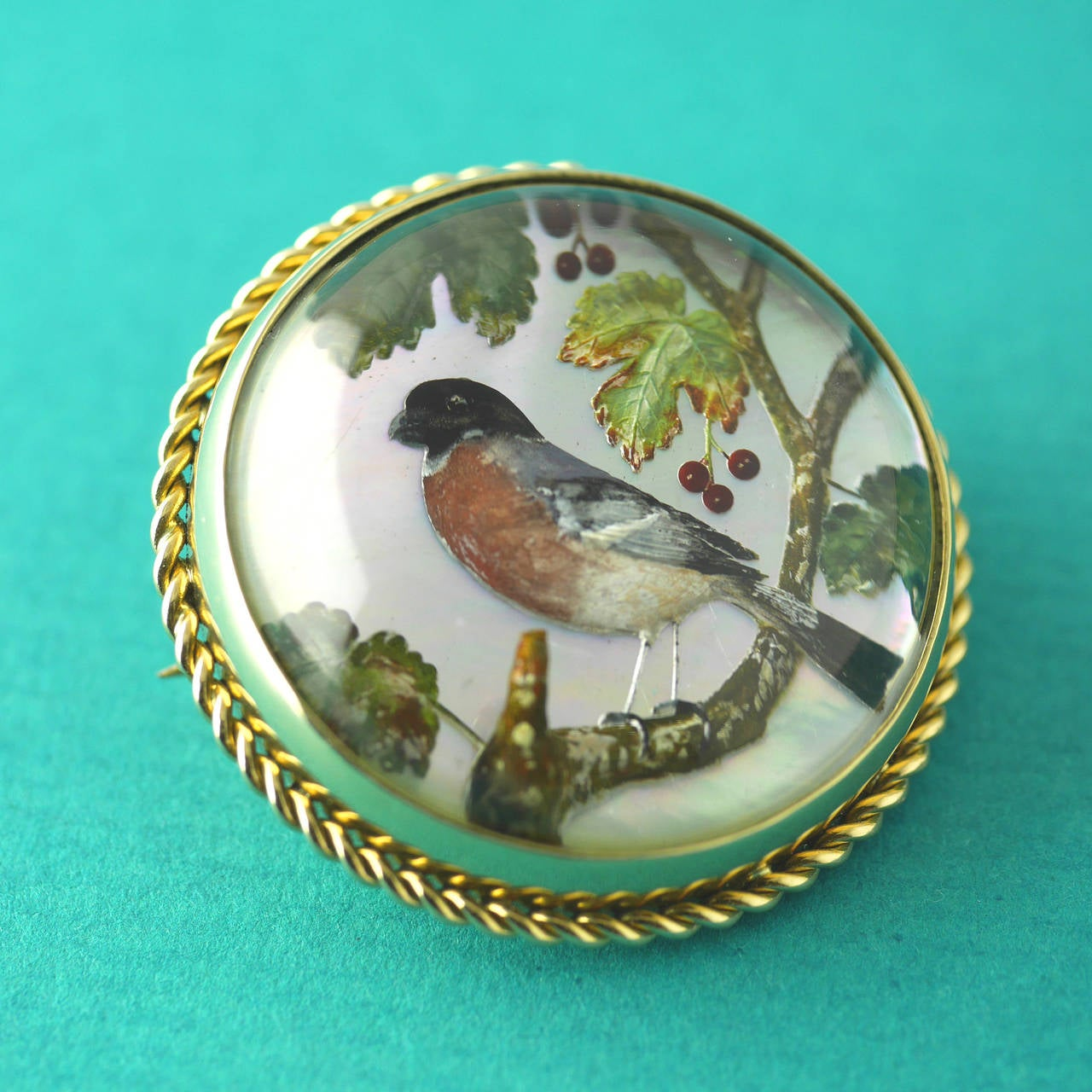 Essex crystal carved and painted showing a bird upon a cherry tree branch. Set on a mother of pearl background in 18kt gold. 