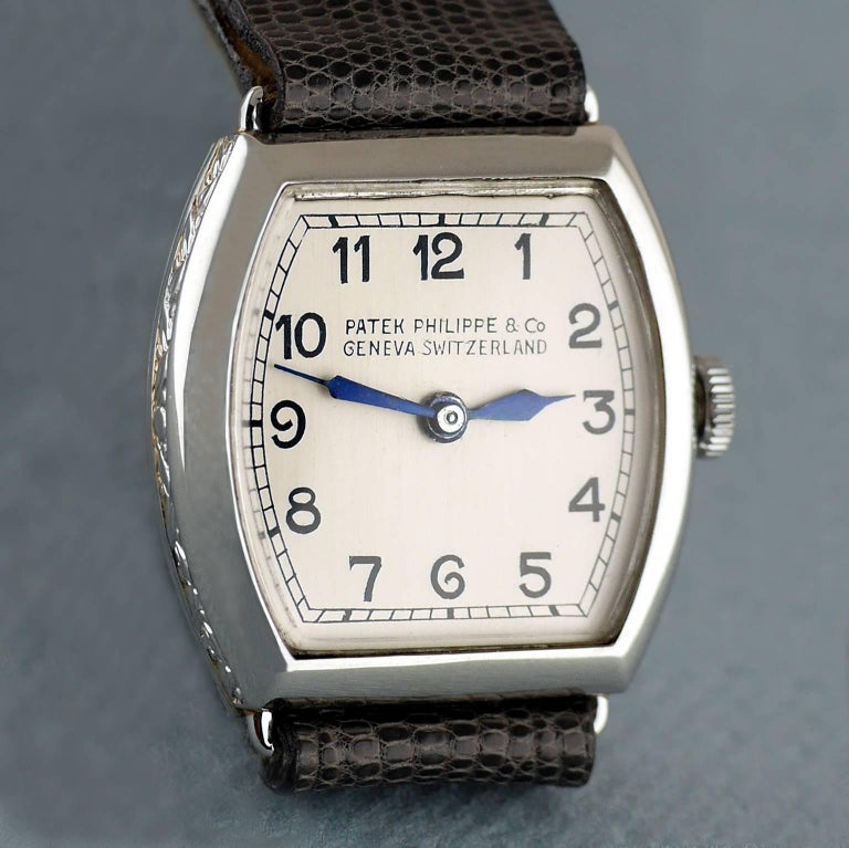 An Art Deco ladies vintage wristwatch by Patek Philippe made in 1938.Very few examples were made in a Tonneau shaped case and even fewer in Platinum.   Platinum Tonneau shaped case, with hand crafted chased (engraved) sides.  18 Jewel, round, 8'''85