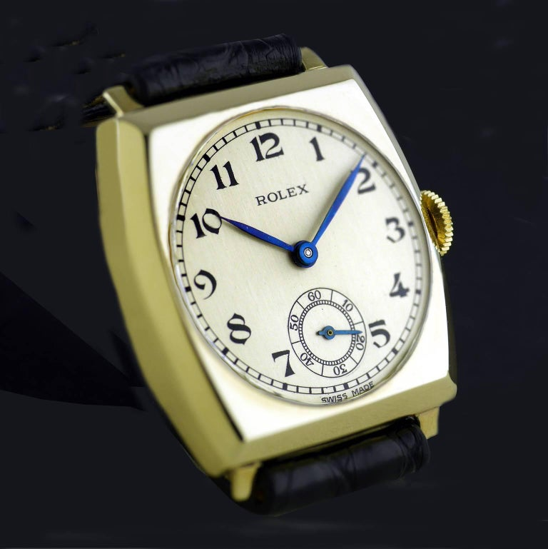 """An Art Deco vintage wristwatch by Rolex made in 1937.  Gold tonneau cushion shaped case marked with Rolex and the """"RWC Ltd"""" lozenge for the Rolex Watch Company Ltd. The snap back gold case is hallmarked for Glasgow Import into the United Kingdom in"""