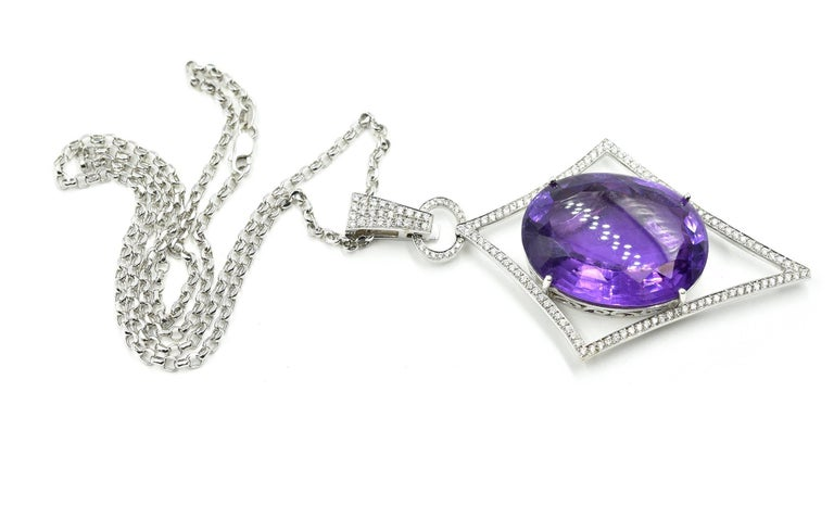 This is a fantastic design! Featured is a jaw-dropping oval mixed cut 53ct amethyst prong set in the 14k white gold navette-shaped pendant! The pendant is shaped like an arrow pointing down, measuring 81.30mm from the bottom of the pendant to the