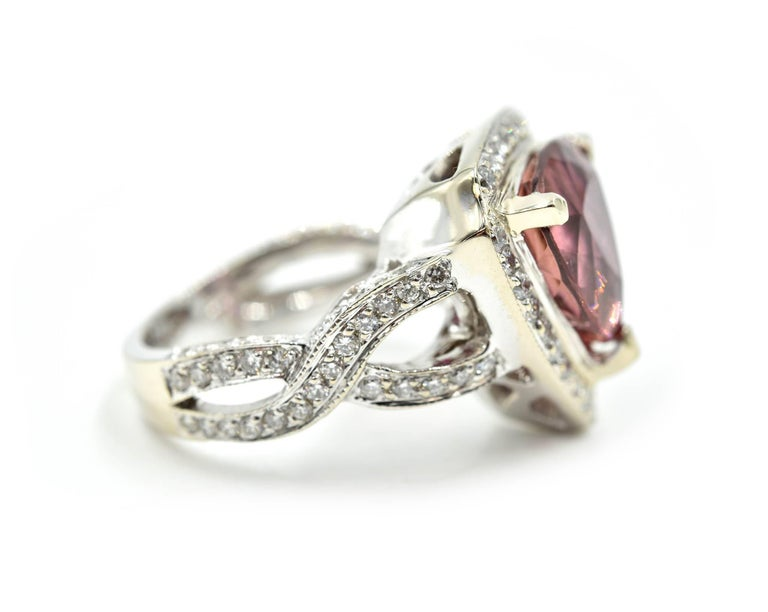 Beauty with an extra dazzle! This is an 18k white gold diamond and pink tourmaline cocktail ring! The diamonds are set on the twisting mounting and halo. The diamonds amount to 117 stones and weigh 1.44 carats. Each diamond is graded G-H in color