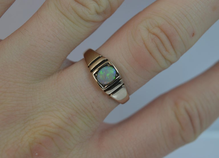 A beautiful true antique solid 15ct gold and opal ring.  Designed with an oval shaped natural opal. 4.8mm x 5.8mm stone.  Set into a rectangular head with two deep columns to each side making the piece a simple yet stylish ring.   CONDITION ; Very