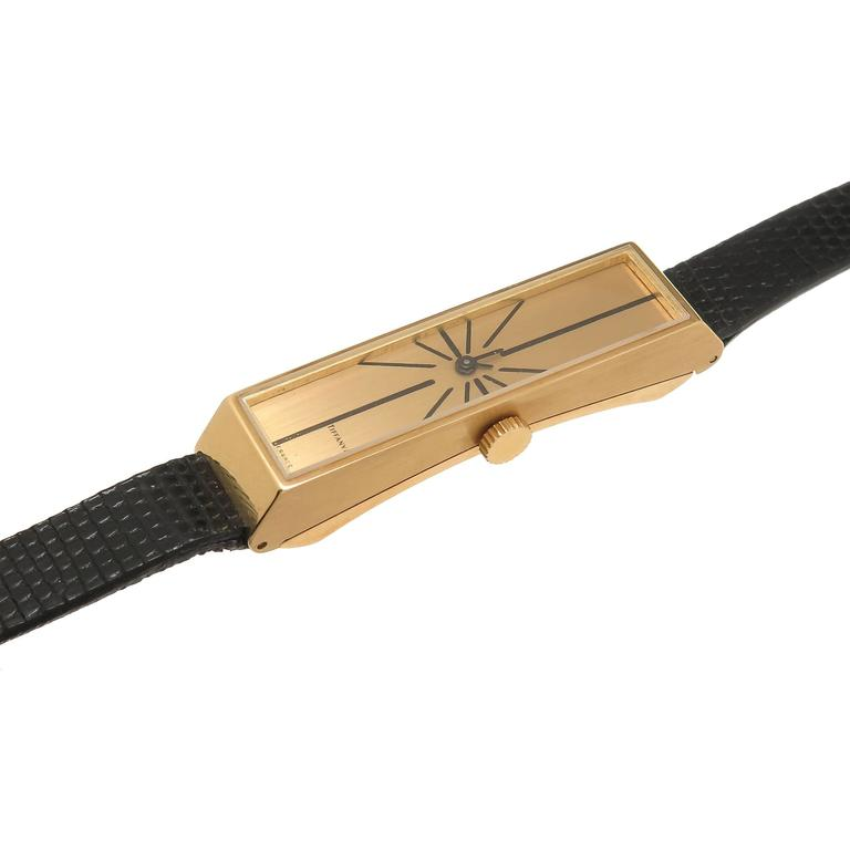 Circa 1970s Tiffany & Company France, 18K Yellow Gold Elongated Wrist watch measuring 1 3/4 inch in length 3/8 inch wide and having a curved to fit the wrist case back. Manual wind 17 Jewel UTI movement, original Gold Dial. New Tiffany & Company