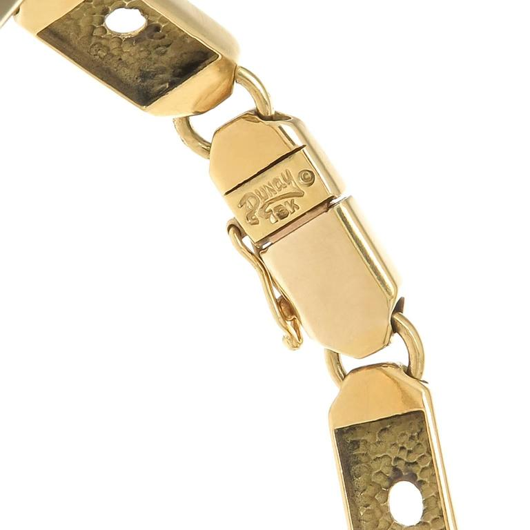 "Circa 1980s Henry Dunay 18K Yellow Gold flexible link Bracelet, measuring 6 3/4 inch in length and 5/16 inch wide. The center of the bracelet spells out ""LOVE"""