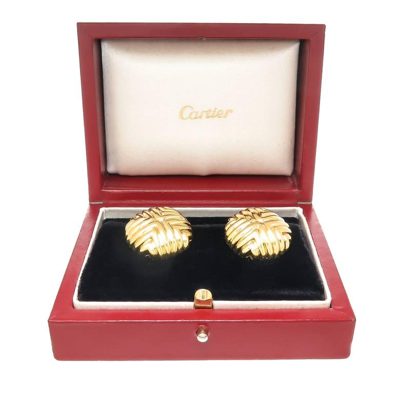 Circa 1980 Cartier 18K Yellow Gold Button Form Earrings, measuring 7/8 inch in diameter and 3/16 inch thick.Having an omega clip back to which a post can be easily added if desired. Signed, Numbered and in the original Cartier Presentation box.
