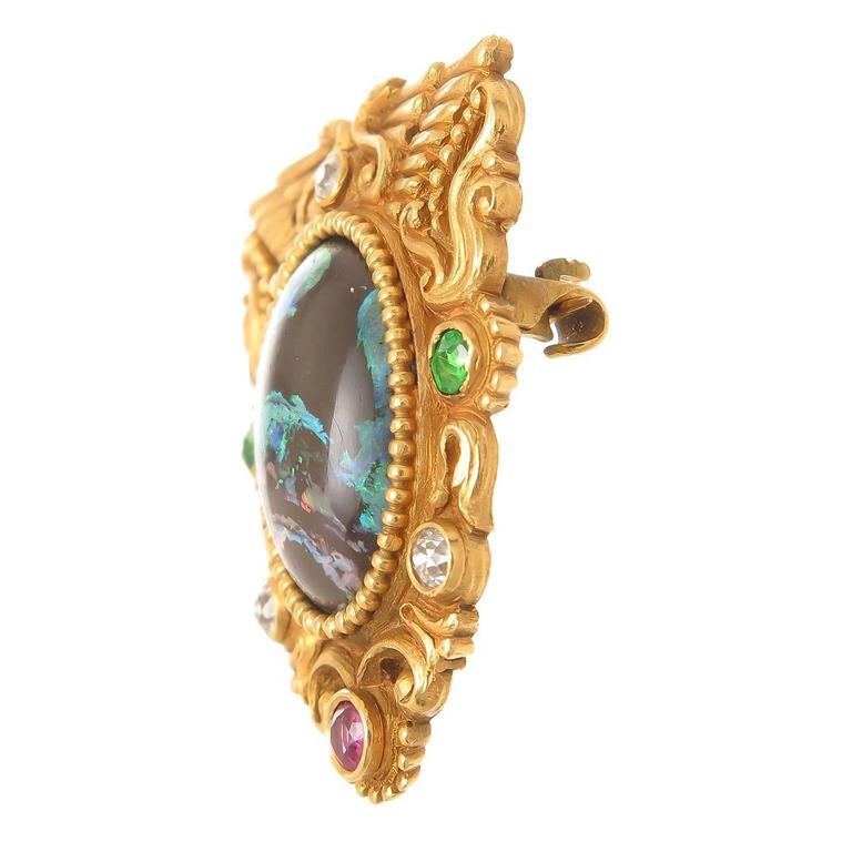 Circa 1910 Attributed to Marcus & Company but not signed, 14K yellow Gold Beautiful mint almost unworn condition, deeply hand chased and detailed on both sides and measuring 1 1/4 inch X 1 inch, centrally set with a fine Black Opal and further set