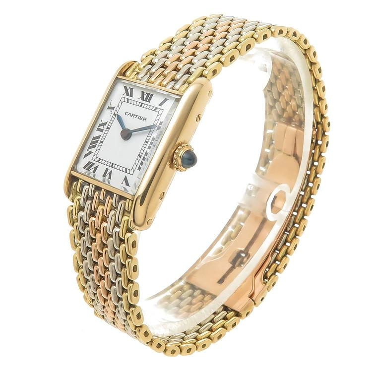 Circa 1980 Cartier Ladies Tank Watch on a Tri Color Gold Cartier bracelet. 25 X 23 MM 18K Yellow Gold Case, Mechanical, manual wind movement, White Enamel Dial with Black Roman Numerals, Sapphire Crown. 5/8 inch wide White, Yellow and Rose Gold Link