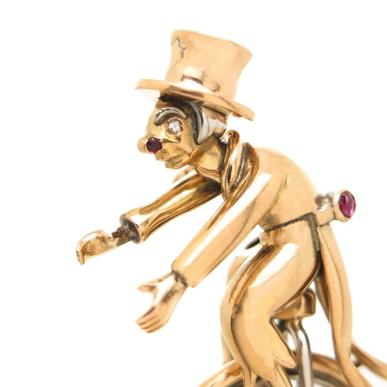 Circa 1940s 18K Yellow Gold Clown on a unicycle Brooch, measuring 2 inch in length 1 1/8 inch wide and weighing 20 Grams. Having nice Dimensional detail on both sides of the brooch with a double clip pin. Set with Emeralds, Rubies and Sapphires.