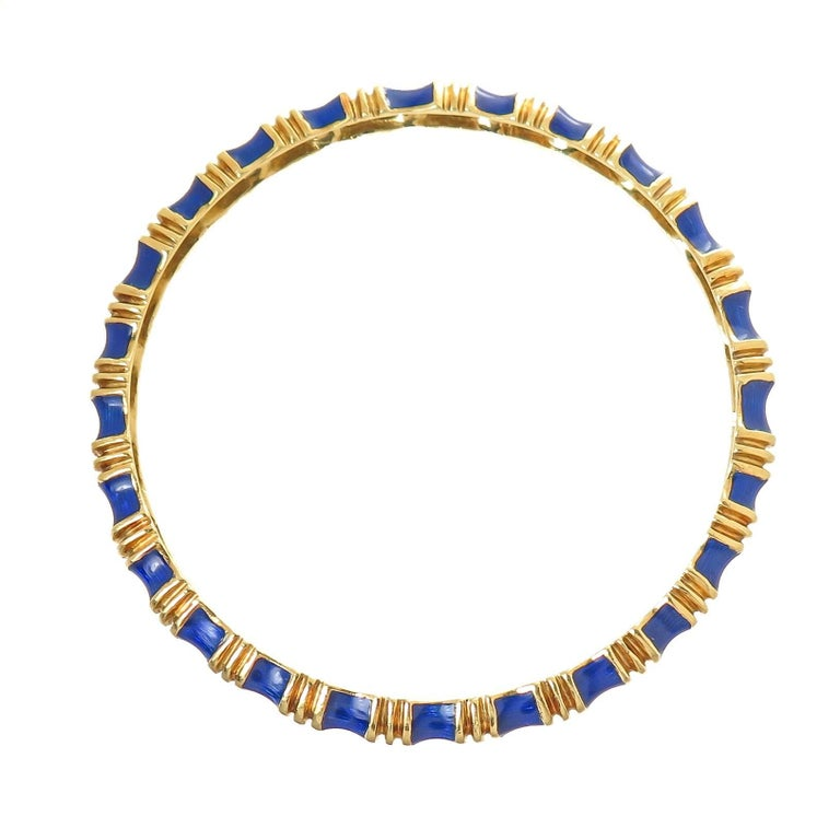 Circa 1970s Tiffany & Company 18K yellow Gold Bangle Bracelet, having a ribbed design and finished in a Cobalt Blue Guilloche Enamel. Measuring 1/4 inch wide with an inside measurement of 7 1/2 inch. The bracelet weighs 38 Grams and is in excellent