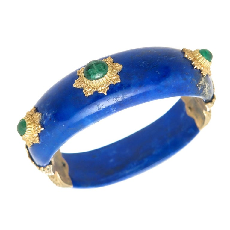 Circa 1970 Buccellati Lapis Lazuli Bangle Bracelet, with 18K yellow Gold Mounted Sections set with Cabochon Emeralds, the largest of which are approximately 1 Carat.  Measuring 5/8 inch wide,  3/8 inch thick and having an inside measurement of 6