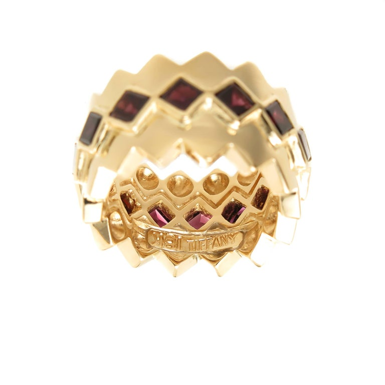 Circa 1980s Tiffany & Company 18K Yellow Gold Band ring, measuring 1/2 inch wide and set all the way around the ring with square cut Garnets. Nice solid construction and weight of 19.3 Grams. Finger size = 6. Excellent, near unworn condition.