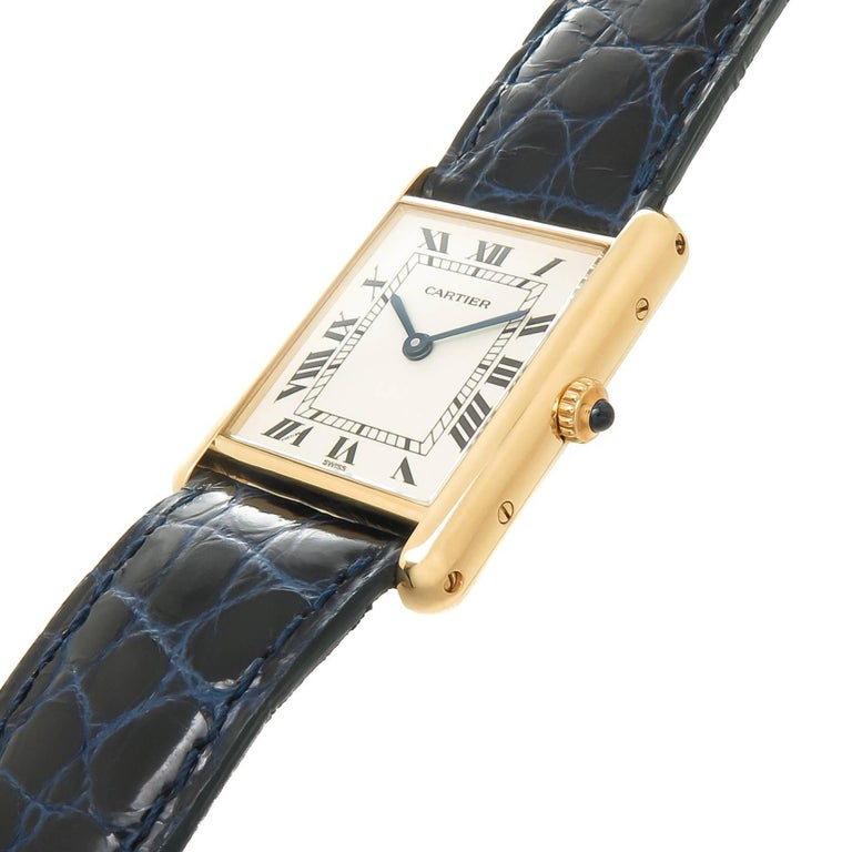 Circa 2000 Cartier Classic Tank Wrist Watch, 30 X 23 MM 18K yellow Gold case, quartz movement, White Dial with Black Roman Numerals, Sapphire Crown. New Cartier Dark Blue Croco grain Strap with Cartier 18K yellow Gold Tang Buckle. Watch length 8 1/4