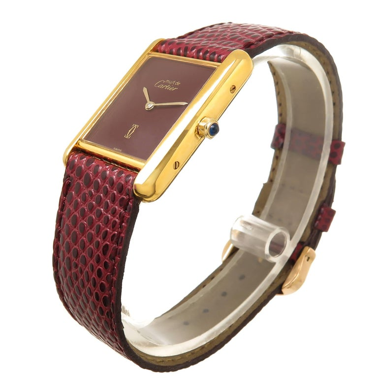 Circa 1990 Cartier Vermeil ( Gold Plate Sterling Silver ) Wrist watch, 30 X 24 M.M. Case, Quartz Movement, Burgundy Dial and a Sapphire Crown. New Burgundy Lizard strap with original Cartier Gold Plate Tang buckle. Watch length 8 1/2 inches.