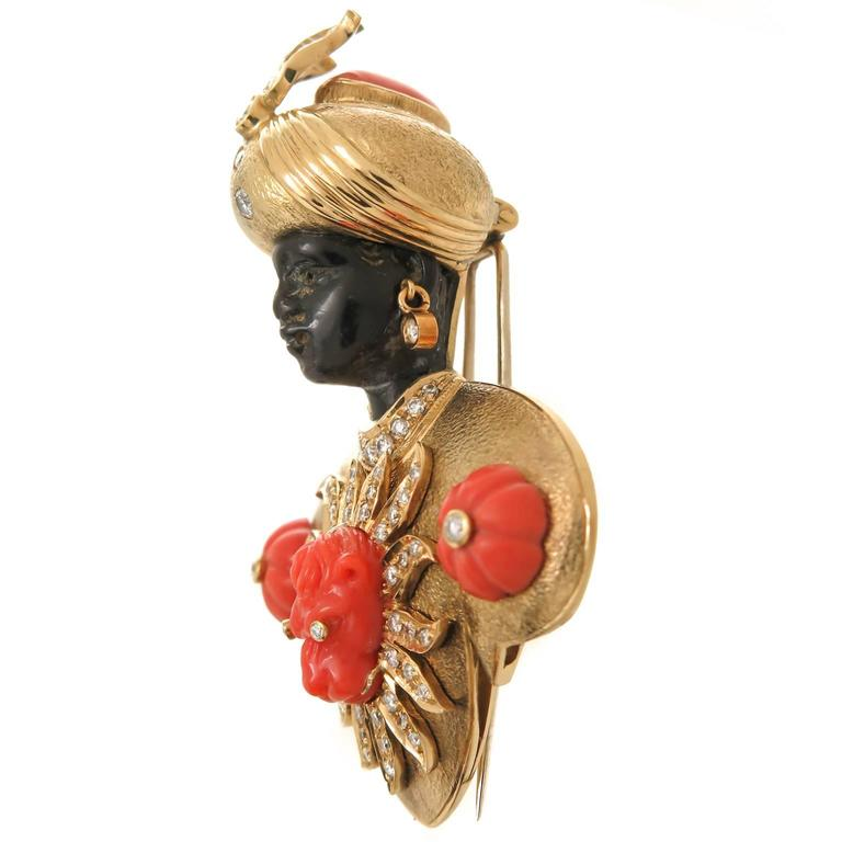 circa 1970s Nardi 18K Yellow Gold and Gem set Blackamoor Brooch. measuring 2 3/4 inch in length and 2 inch wide, having a carved Onyx head with dangling Diamond earrings and Carved Coral decorations and further set with numerous round brilliant cut
