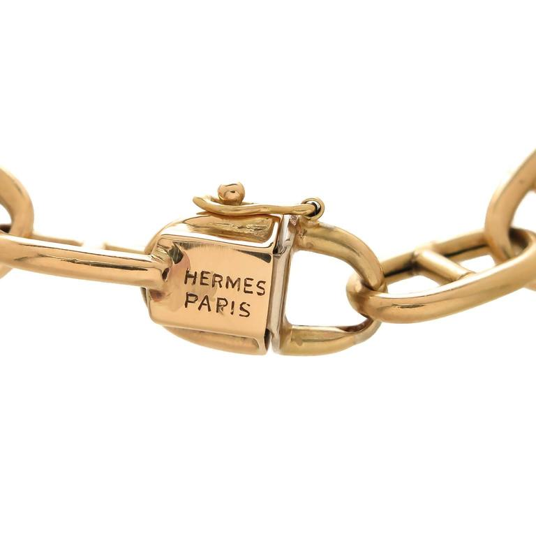 Circa 1960s Hermes Paris, 18K yellow Gold Anchor Link Bracelet, measuring 7 3/4 inch in length and 5/16 inch wide. Solid links, tongue clasp with a safety and a Cabochon Sapphire push piece. Signed and bearing French Hall Mark.