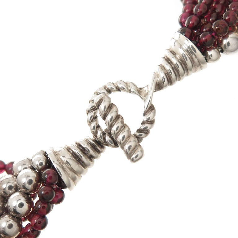 Circa 1990s Tiffany & Company Torsade Necklace, comprised of several strands of Round Garnet and Sterling Silver Beads, measuring 16 Inches in length and 1 inch wide. Having a toggle clasp. Comes in original Tiffany Presentation case.