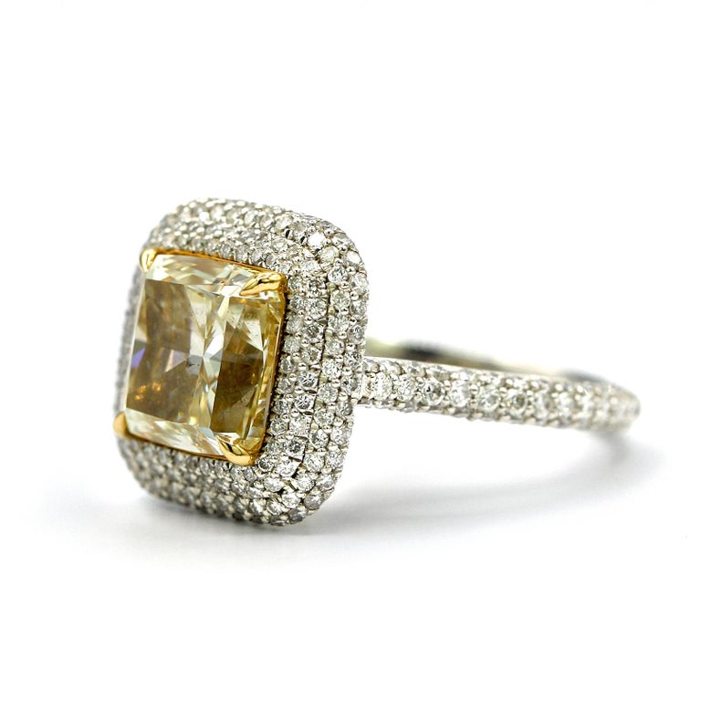 This absolutely stunning 4.25 Carat EGL Certified Fancy Light Yellow Cushion SI1 with 1.35 Carat White Pave Diamonds all around the center stone. Ring Size 6.5 Mounted in Platinum and 18K White Gold.