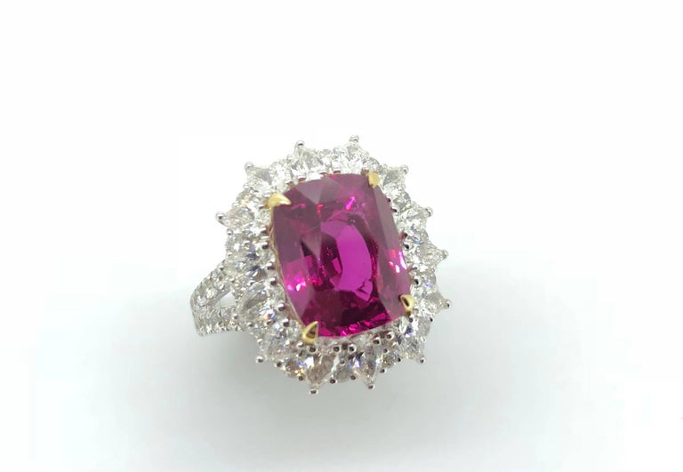 A 7.00 Carat Cushion cut Vivid Pink Sapphire (Heat) Cocktail Cluster Diamond Ring.   Mounted in 18K White and Yellow gold with cluster of pear shape diamonds interspaced by round brilliant cut diamonds. The ring is ornately completed with a diamond