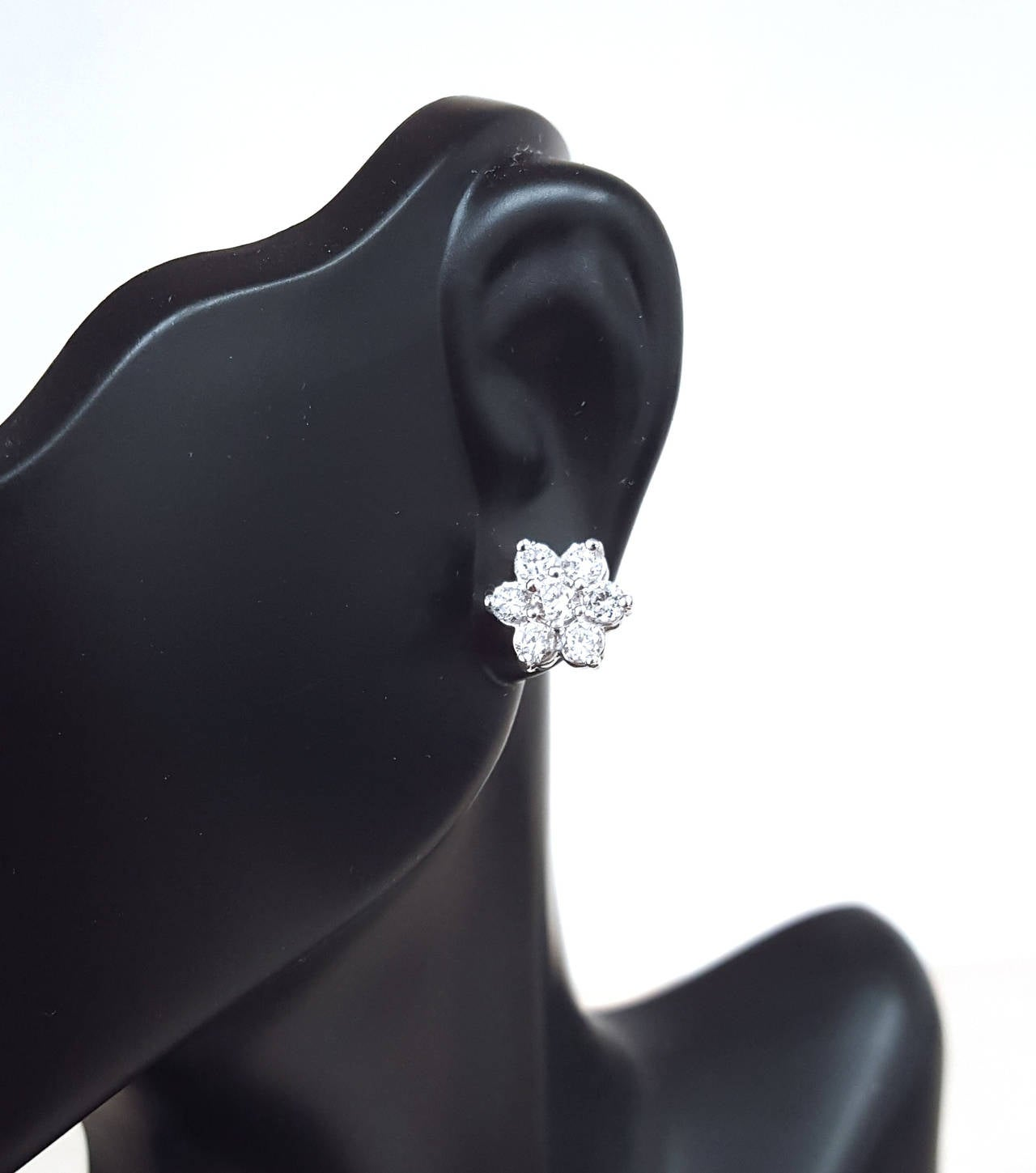 Beautifal cluster diamond earring has a larger 15 pointer diamond in the center and smaller diamonds going around it. 