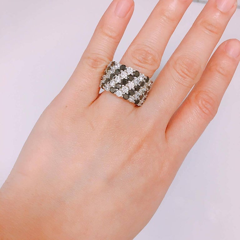 Alternating rows of natural black and white diamonds set in this lovely 18k gold ring.  3.86ct Black diamonds 2.82ct white diamonds  Approx total weight: 6.68cts Diamond Color: E-F Diamond Clarity: Vs  Cut: Excellent  As noted we are vetted and