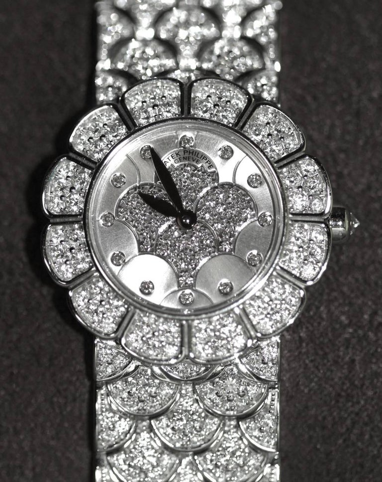 Stunning pre-owned Patek Philippe Ladies Watch.  Barely worn, the watch is like new.  Ref: 4872/2G-001 Caliber: E-15 Quartz  Movement Jewels: 6R Case and dial set with 202 diamonds: 2.28 Ct Dial: Pavé-set diamond bezel in the form of petals Case: