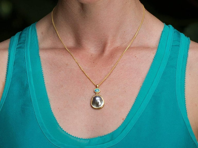 A glowing Perlas del Mar de Cortez Mabe Pearl meets its match with a Hopkins Australian Lightening Ridge Opal in this pendant with hammered 22 and 18 karat reclaimed gold. The bail is accented with a VS Canadian diamond. Accompanied by a 18 karat