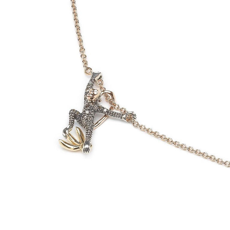 This playful necklace by Bibi van der Velden features two diamond-set Sterling Silver monkeys with 18k Rose Gold faces and tails, swinging from an 18k Rose Gold chain. Whilst one monkey clutches onto a bunch of 18k yellow gold bananas, the other