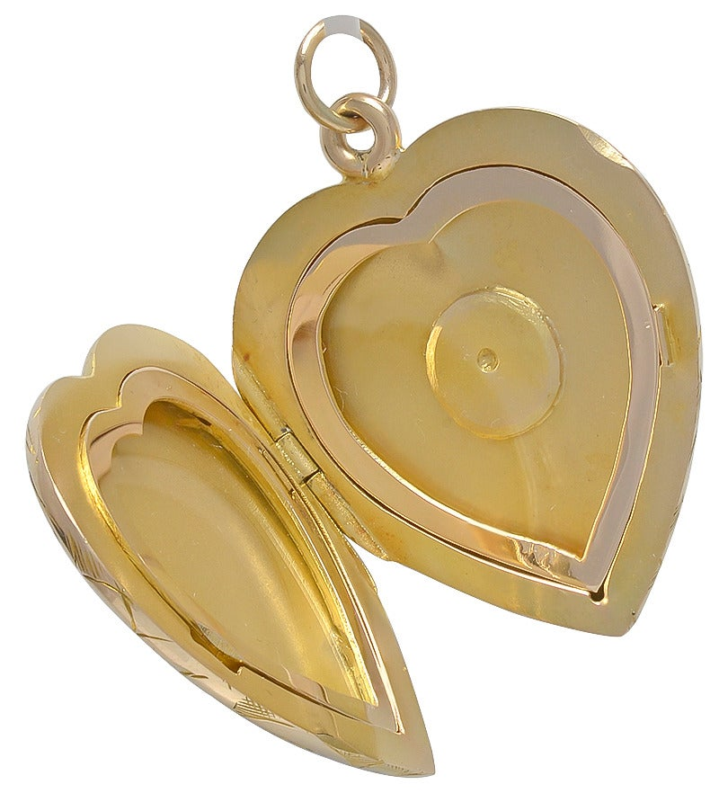 Exceptional antique figural heart locket. All over deeply engraved flowered leaf pattern on both front back. 14k yellow gold. Opens to hold two pictures, with original gold bezels. 1 1/4