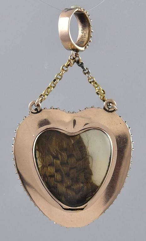 "The ultimate romantic and haunting ""Lover's Eye"" piece of jewelry:  a figural heart-shaped drop, embracing a finely drawn enamel eye, surrounded by seed pearls, and suspended with two fine chains from a pearl bale.  The hinged compartment in the"