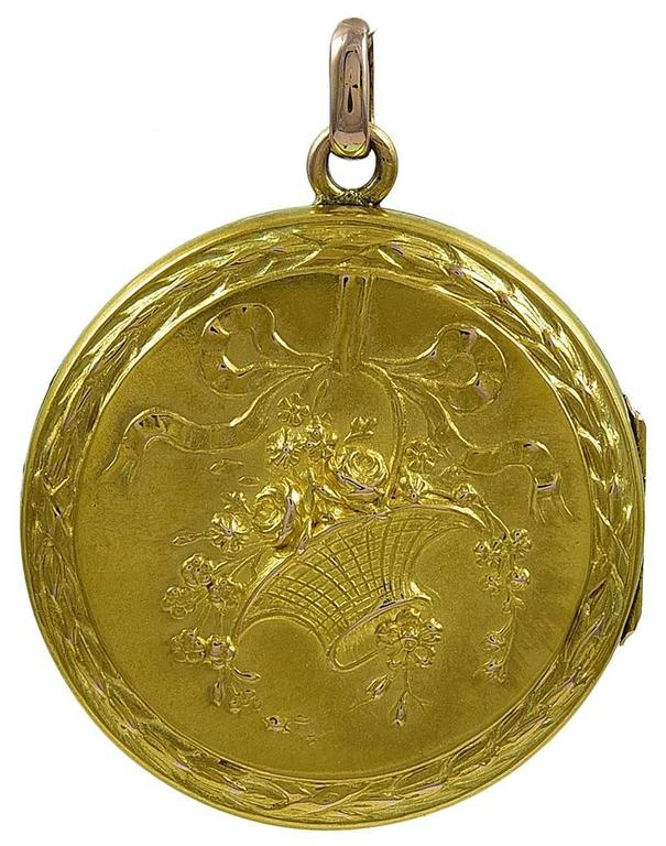 Very fine and exceptionally lovely round gold hinged locket.   Embossed basket of flowers, with a flowing ribbon; applied reed and ribbon border.  Reverse side has same reed and ribbon border, surrounding the original beveled glass.  1 1/4